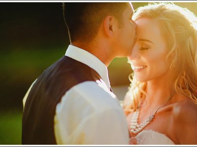 Golden light and groom kissing bride