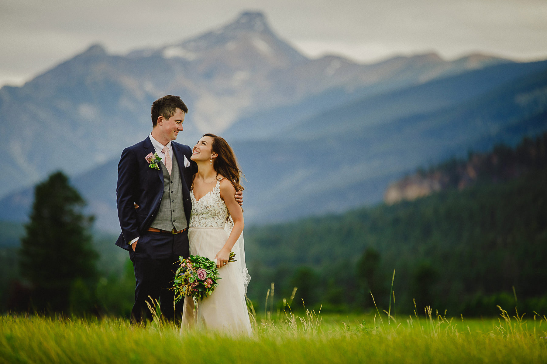 Bride and groom enjoying each others company with stunning mountain backdrop at Panorama