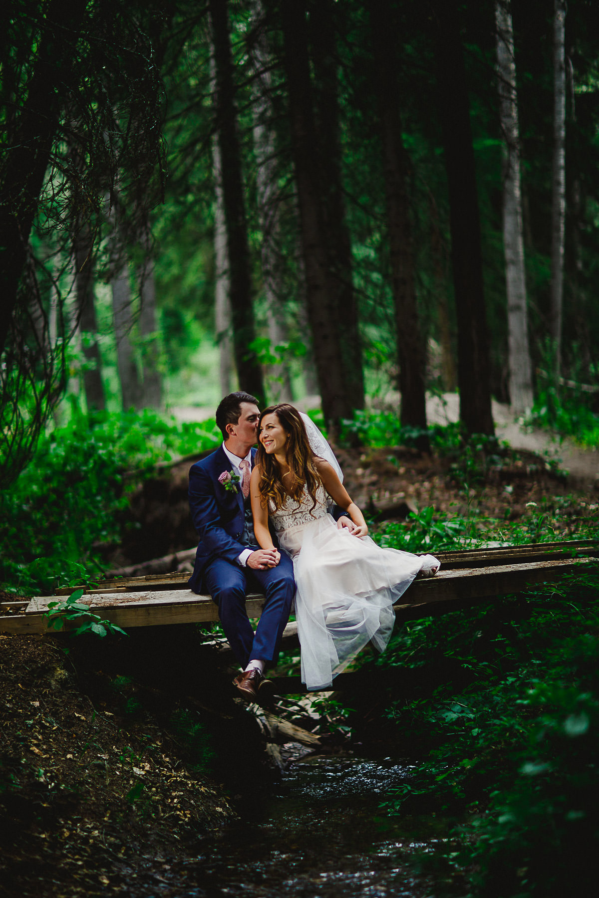 Bride and groom sitting on footbridge in lovely forest at Panorama Mountain Resort