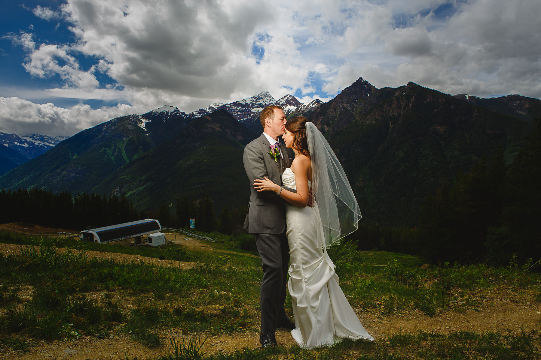 Bride and groom with ski lift in background at Panorama Ski Resort