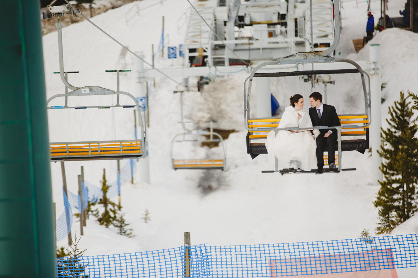 Bride in white cape on chairlift at Panorama Mountain Resort
