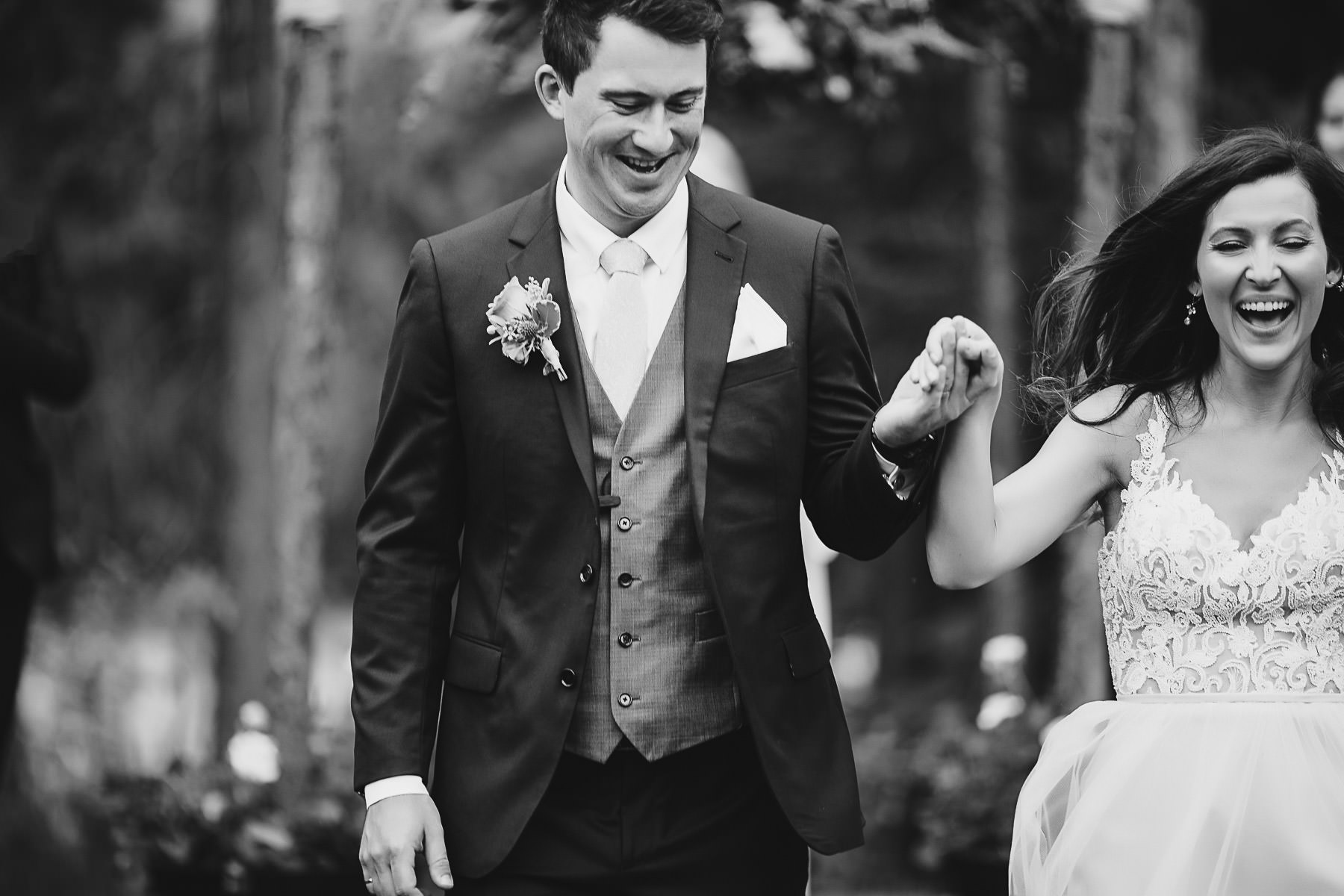 Groom and bride laughing while exiting from their wedding ceremony at Panorama Mountain Resort