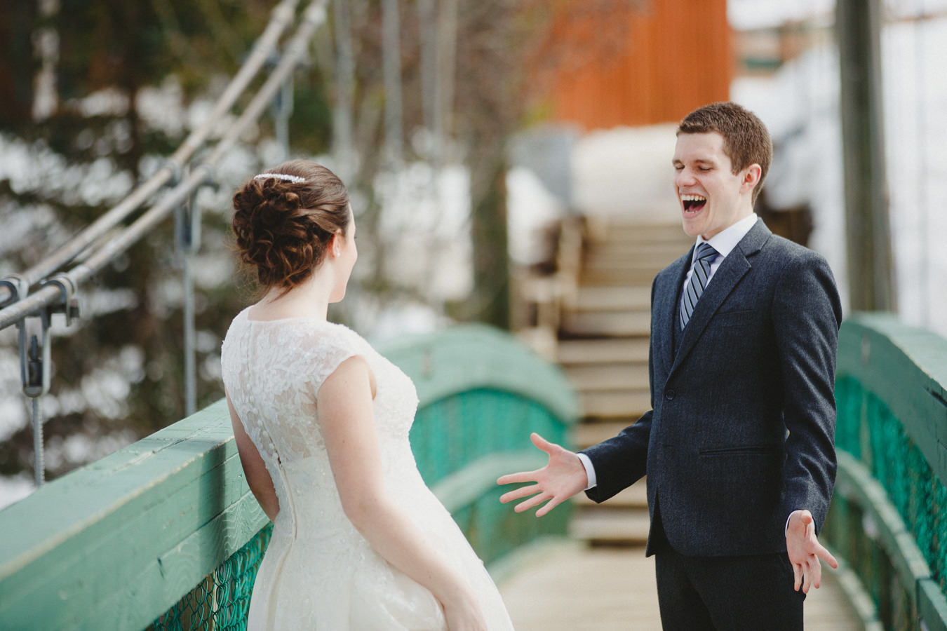 Groom reacting to seeing bride for first time on the pedestrian bridge at Panorama Mountain Resort