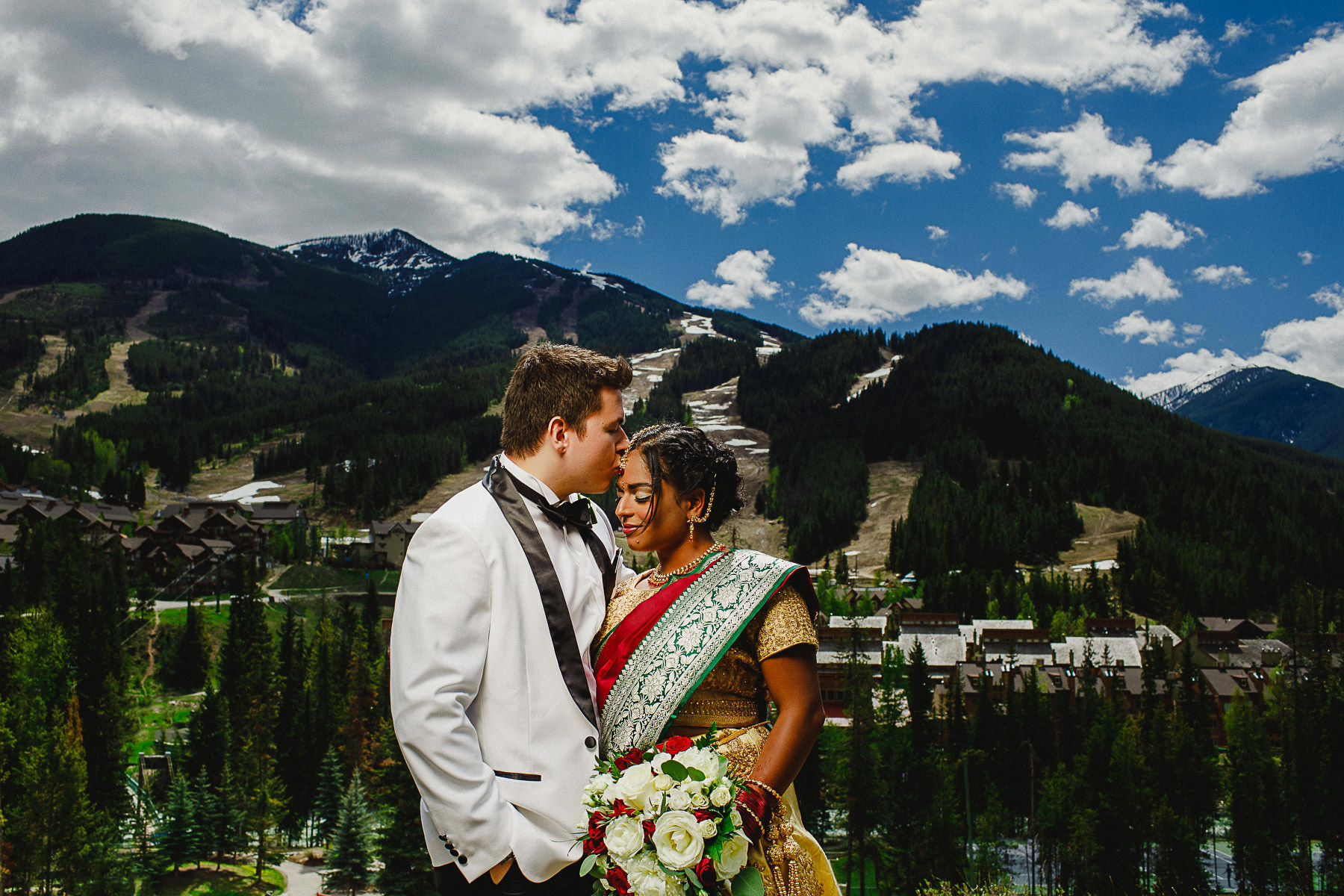 Groom tenderly kissing his bride's forehead with Panorama ski hill in background