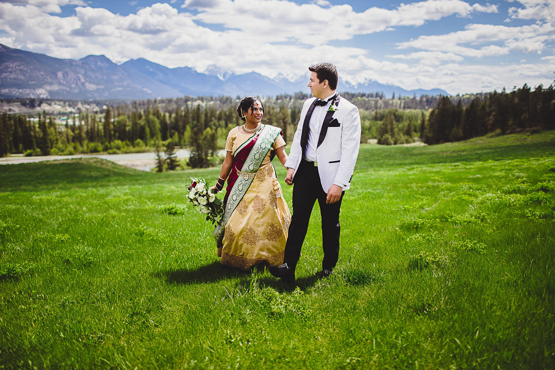 Indian bride and her groom walking through field near Panorama Mountain Resort