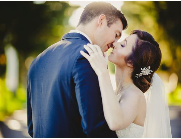 Bride and groom kissing in beautiful light