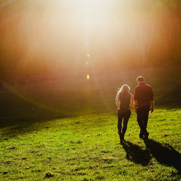 Young couple walks holding hands in sunset