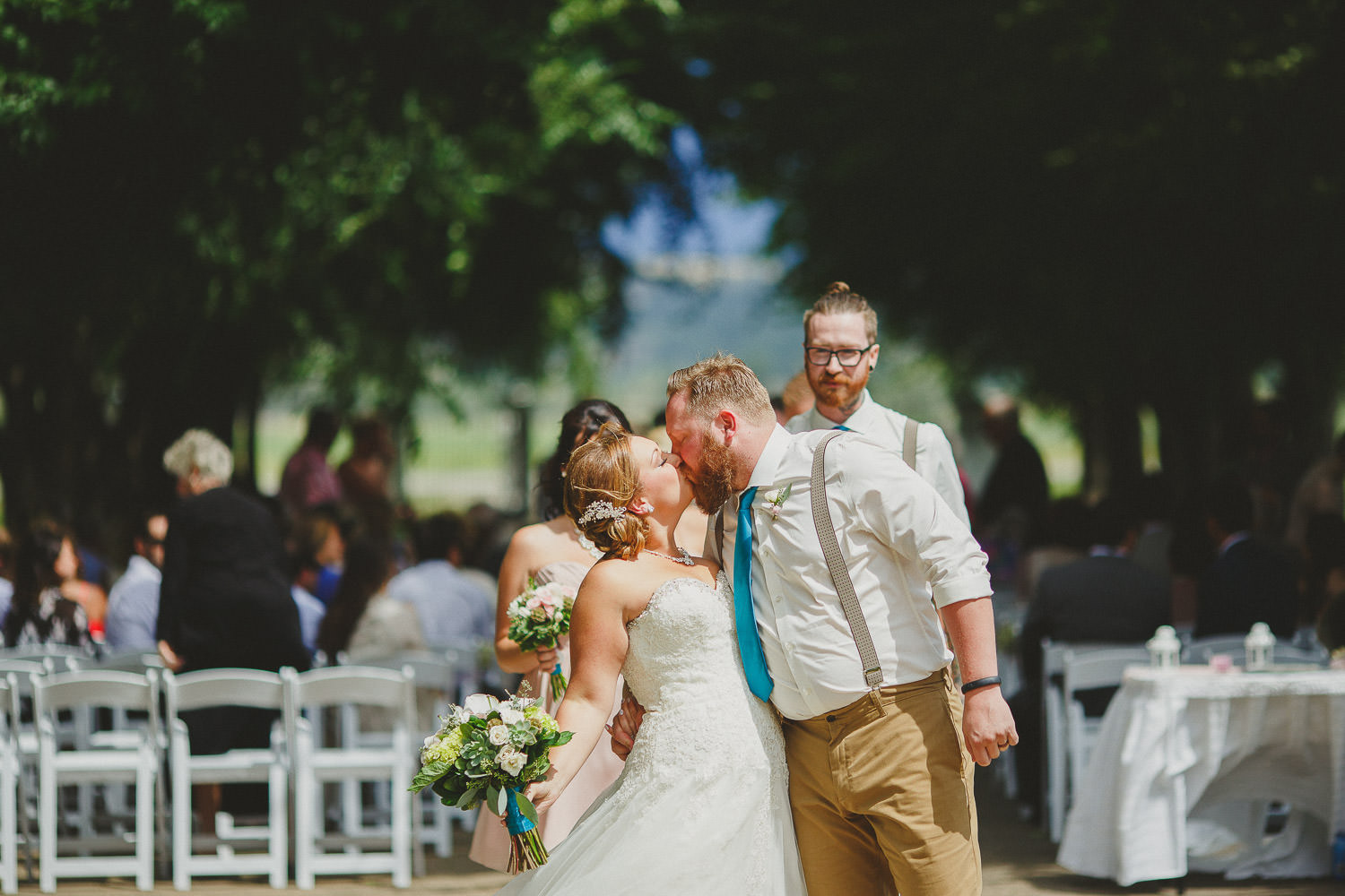 Bride and groom exchange kiss at end of aisle after ceremony