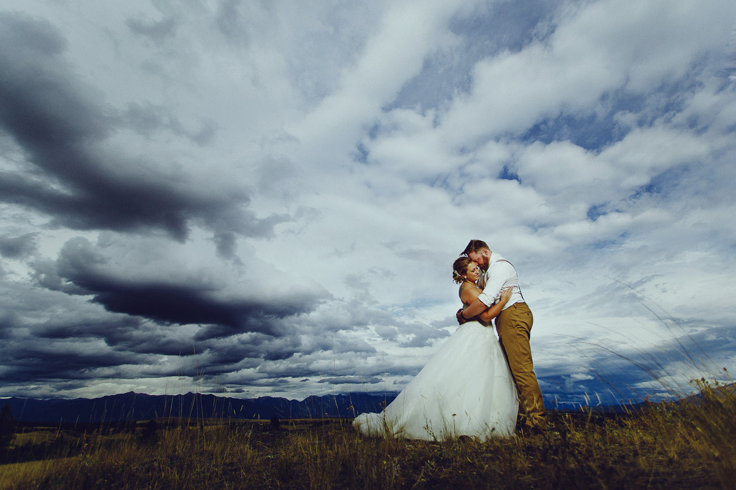 dramatic skies behind bride and groom at St Eugene Mission
