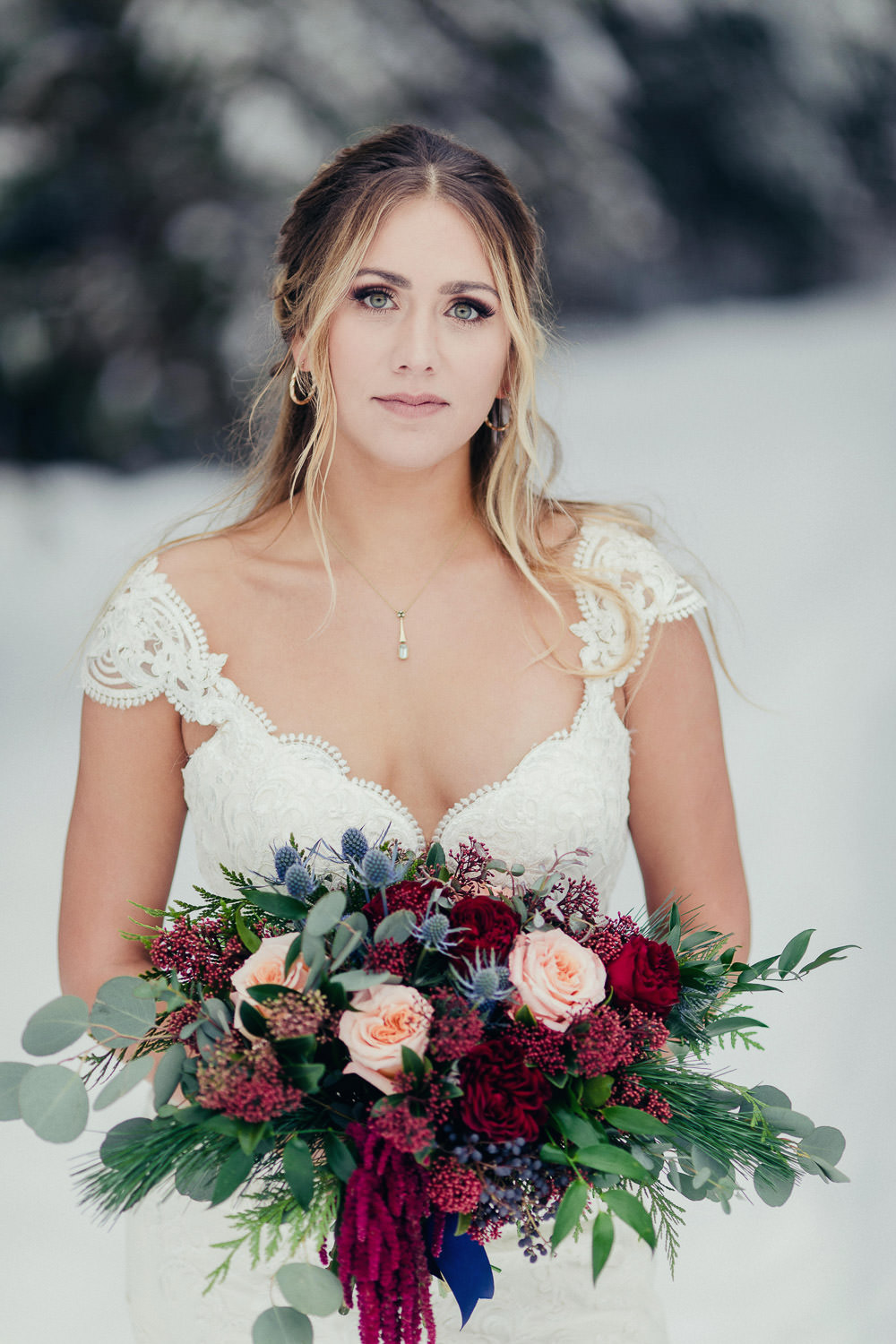 Winter bride holding stunning floral arrangement